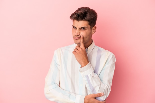 Young caucasian man isolated on pink background unhappy looking in camera with sarcastic expression.