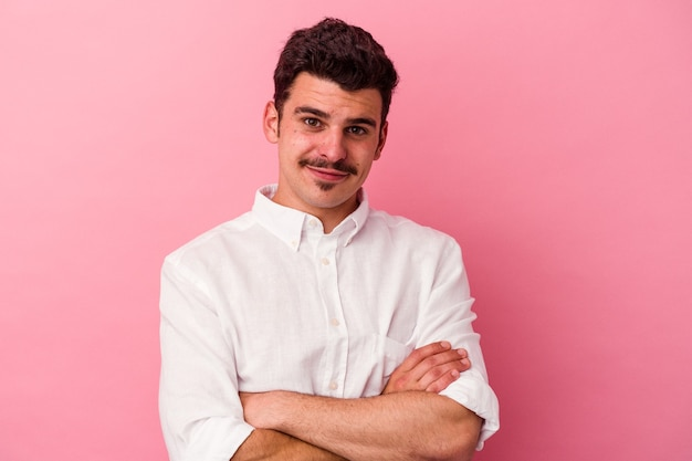 Young caucasian man isolated on pink background who feels confident, crossing arms with determination.