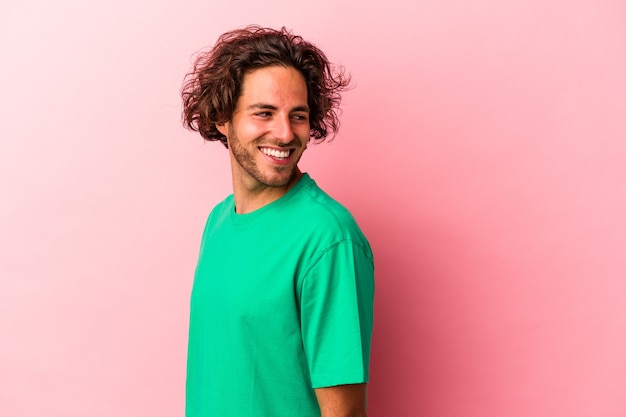 Young caucasian man isolated on pink bakcground looks aside smiling, cheerful and pleasant.