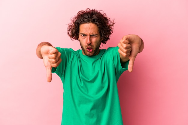 Young caucasian man isolated on pink bakcground showing thumb down and expressing dislike.
