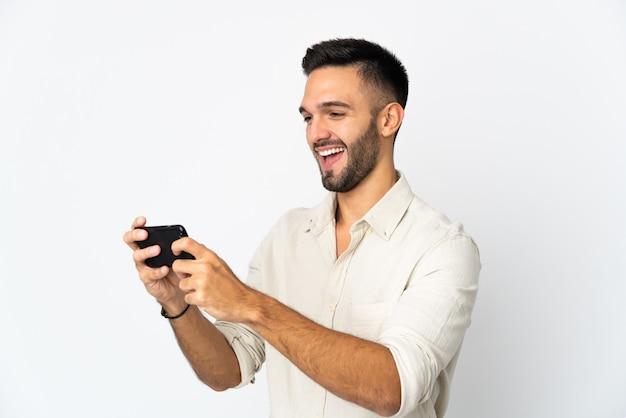 Молодой кавказский человек изолирован, играя с мобильным телефоном