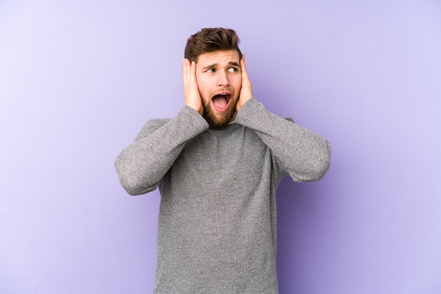 Young caucasian man isolated on purple background covering ears with hands trying not to hear too loud sound.