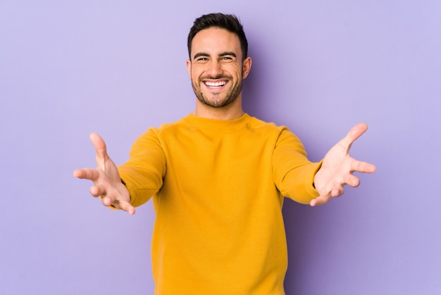 Young caucasian man isolated on purple background feels confident giving a hug to the camera.