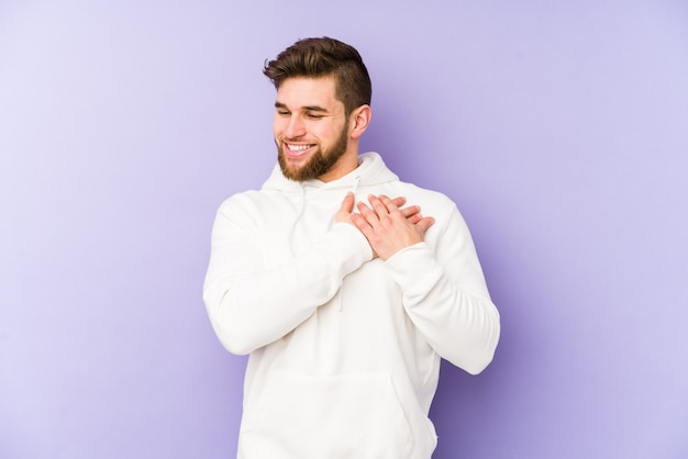 Young caucasian man isolated on purple background has friendly expression, pressing palm to chest. love concept.