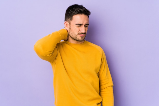 Young caucasian man isolated on purple background having a neck pain due to stress, massaging and touching it with hand.