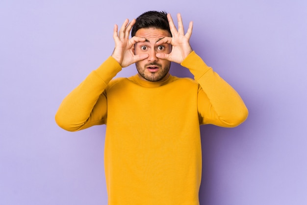 Young caucasian man isolated on purple background keeping eyes opened to find a success opportunity.