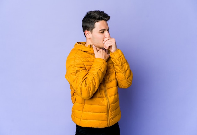 Young caucasian man isolated on purple background suffers pain in throat due a virus or infection.