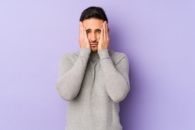 Young caucasian man isolated on purple background whining and crying disconsolately.