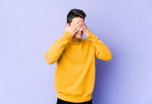 Young caucasian man isolated on purple wall afraid covering eyes with hands.