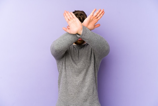 Young caucasian man isolated on purple wall keeping two arms crossed, denial concept.