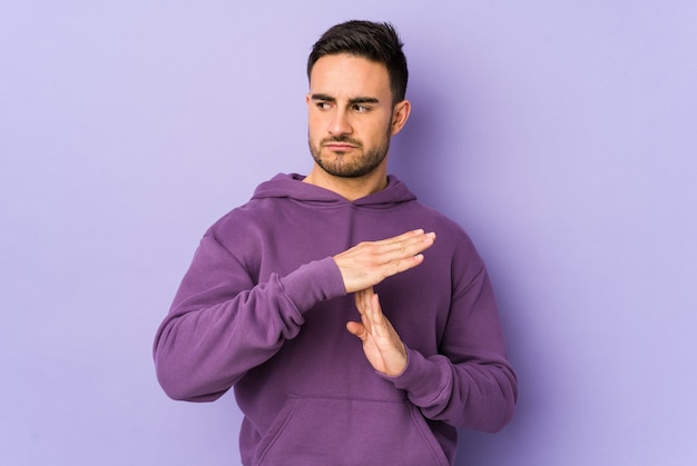 Young caucasian man isolated on purple wall showing a timeout gesture.