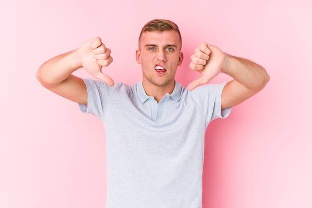 Young caucasian man isolated showing thumb down and expressing dislike.