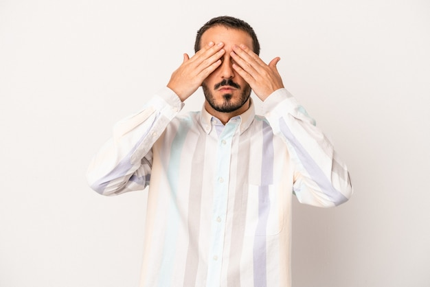 Young caucasian man isolated on white background afraid covering eyes with hands.