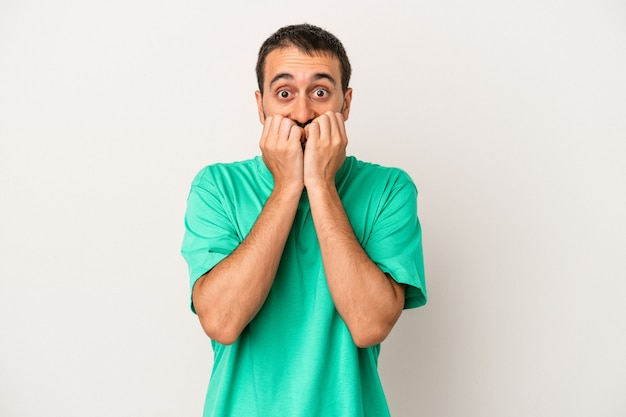 Young caucasian man isolated on white background biting fingernails, nervous and very anxious.