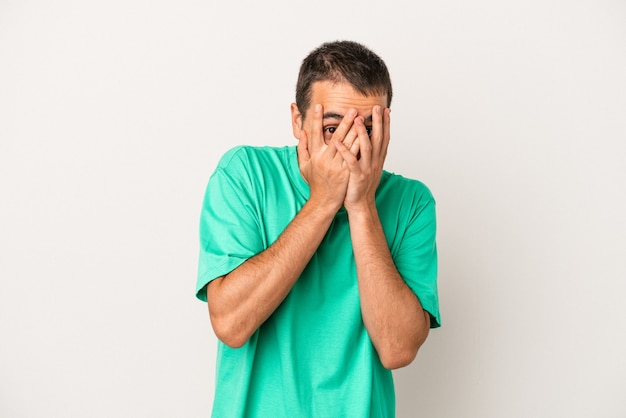 Young caucasian man isolated on white background blink at the camera through fingers, embarrassed covering face.