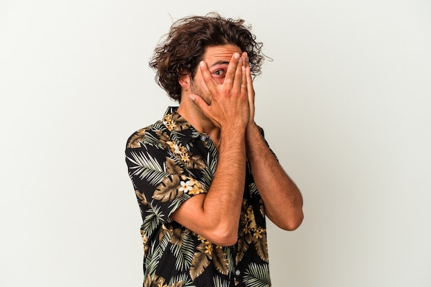 Young caucasian man isolated on white background blink through fingers frightened and nervous.