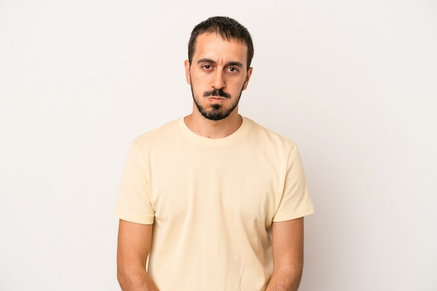 Young caucasian man isolated on white background blows cheeks, has tired expression. facial expression concept.