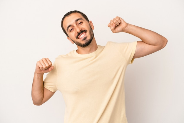 Young caucasian man isolated on white background celebrating a special day, jumps and raise arms with energy.