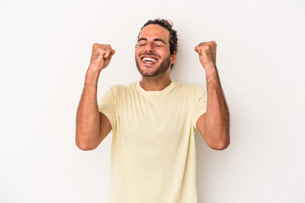 Young caucasian man isolated on white background celebrating a victory, passion and enthusiasm, happy expression.