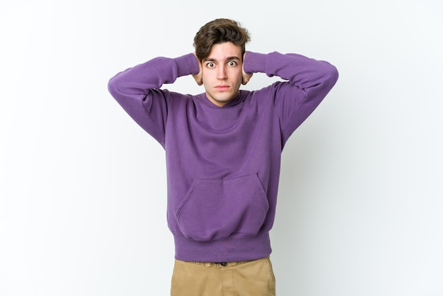 Young caucasian man isolated on white background covering ears with hands trying not to hear too loud sound.