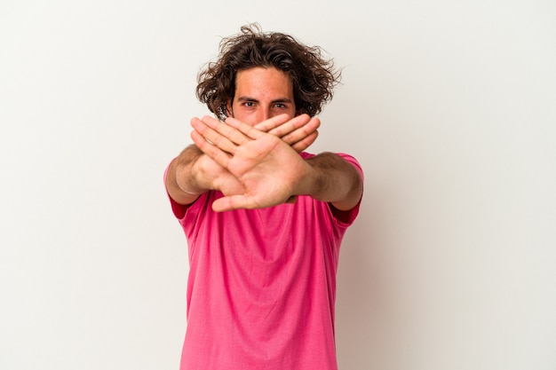 Young caucasian man isolated on white background doing a denial gesture