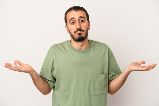 Young caucasian man isolated on white background doubting and shrugging shoulders in questioning gesture.