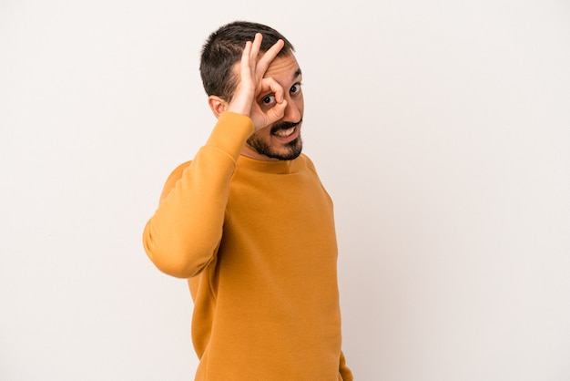 Young caucasian man isolated on white background excited keeping ok gesture on eye.