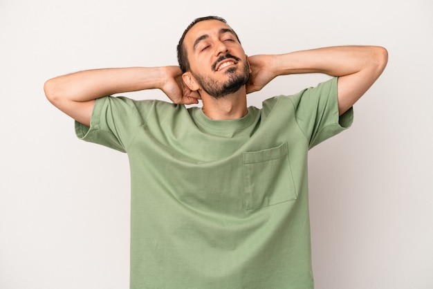 Young caucasian man isolated on white background feeling confident, with hands behind the head.