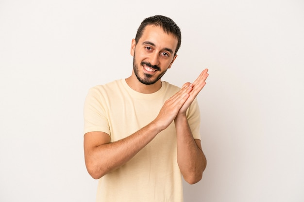 Young caucasian man isolated on white background feeling energetic and comfortable, rubbing hands confident.