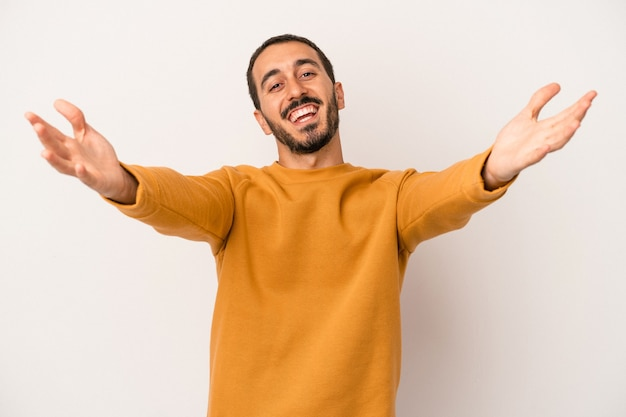 Young caucasian man isolated on white background feels confident giving a hug to the camera.