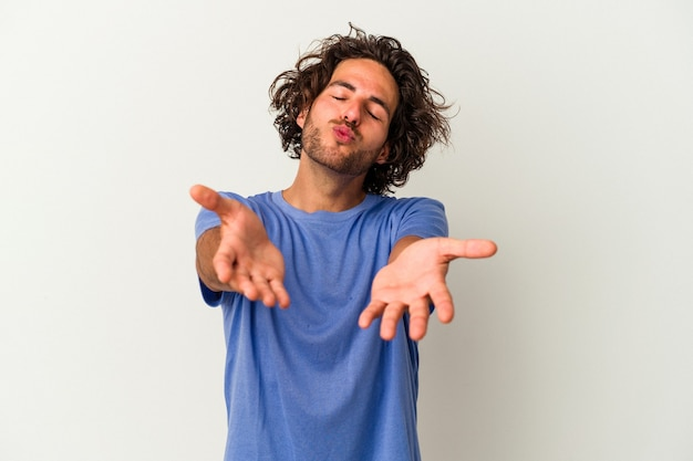 Young caucasian man isolated on white background folding lips and holding palms to send air kiss.