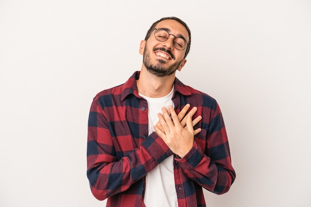 Young caucasian man isolated on white background has friendly expression, pressing palm to chest. love concept.