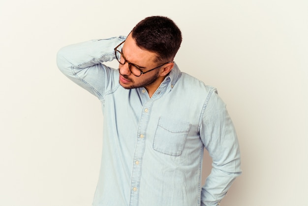 Young caucasian man isolated on white background having a neck pain due to stress, massaging and touching it with hand.