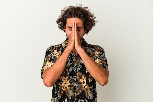 Young caucasian man isolated on white background holding hands in pray near mouth, feels confident.