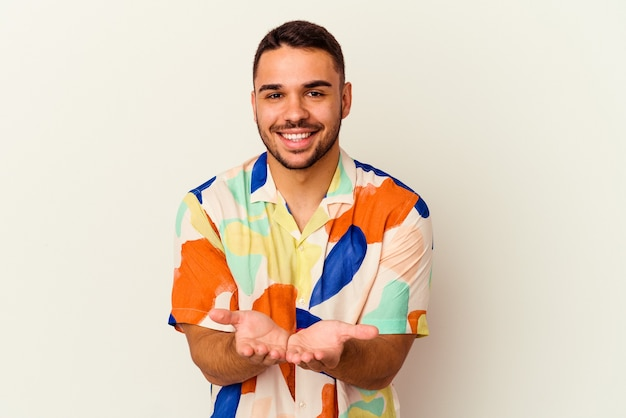Young caucasian man isolated on white background holding something with palms, offering to camera.