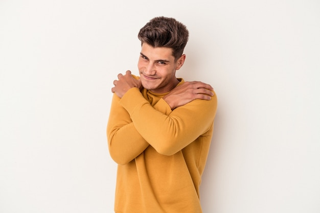 Young caucasian man isolated on white background hugs, smiling carefree and happy.