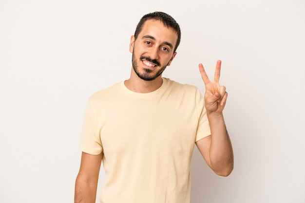 Young caucasian man isolated on white background joyful and carefree showing a peace symbol with fingers.