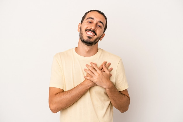 Young caucasian man isolated on white background laughing keeping hands on heart, concept of happiness.