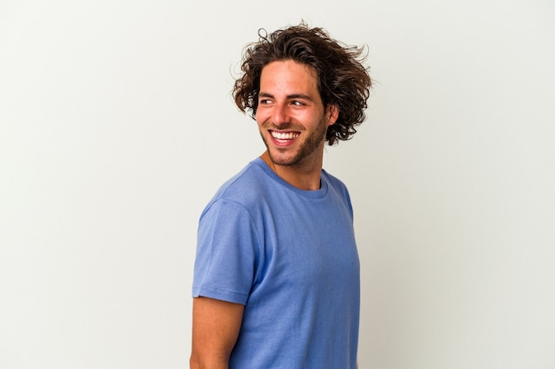 Young caucasian man isolated on white background looks aside smiling, cheerful and pleasant.