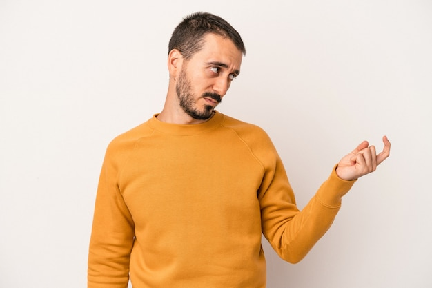 Young caucasian man isolated on white background pointing with finger at you as if inviting come closer.