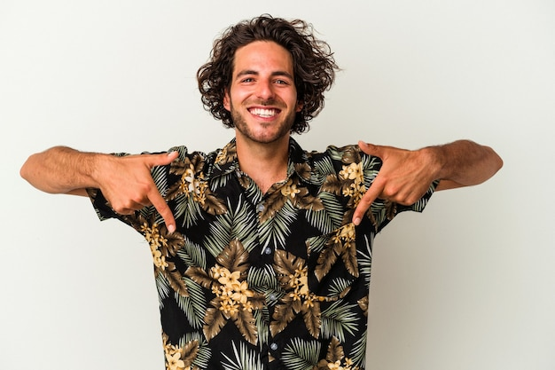 Young caucasian man isolated on white background points down with fingers, positive feeling.