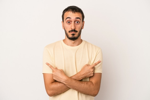Young caucasian man isolated on white background points sideways, is trying to choose between two options.