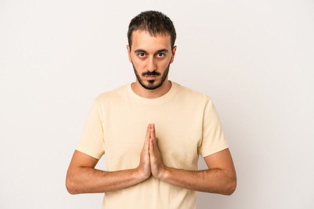 Young caucasian man isolated on white background praying, showing devotion, religious person looking for divine inspiration.