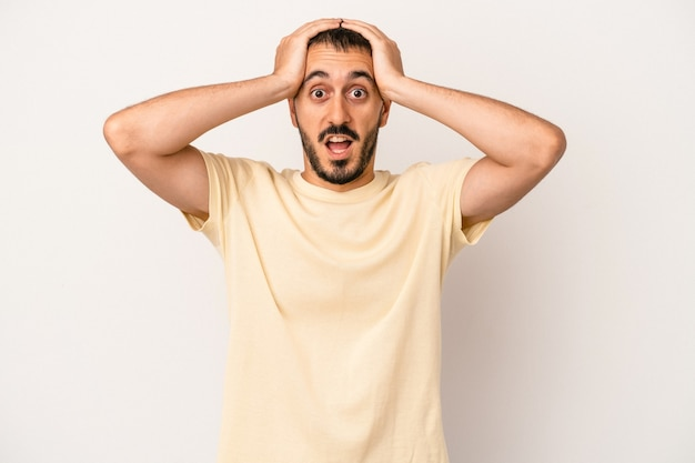 Young caucasian man isolated on white background screaming, very excited, passionate, satisfied with something.