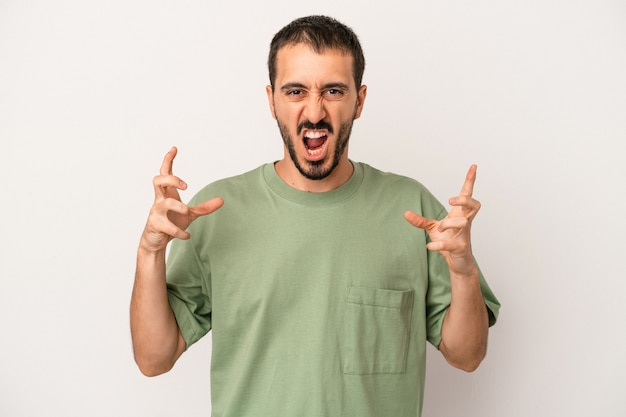 Young caucasian man isolated on white background screaming with rage.