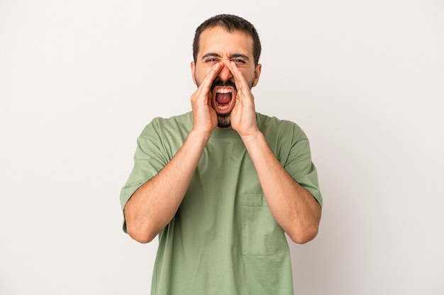 Young caucasian man isolated on white background shouting excited to front.
