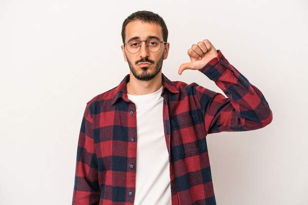 Young caucasian man isolated on white background showing a dislike gesture, thumbs down. disagreement concept.