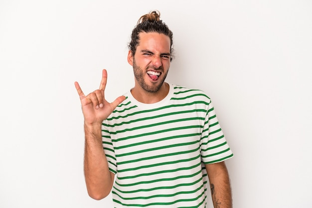 Young caucasian man isolated on white background showing a horns gesture as a revolution concept.