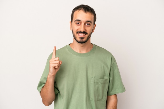Young caucasian man isolated on white background showing number one with finger.