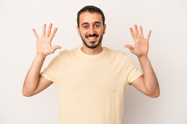 Young caucasian man isolated on white background showing number ten with hands.